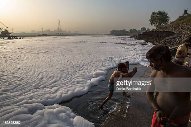 Indian men bathe in an industrial wastefoam polluted section of the Yamuna River on the outskirts of New Delhi on May 24 2013 in New Delhi India The...