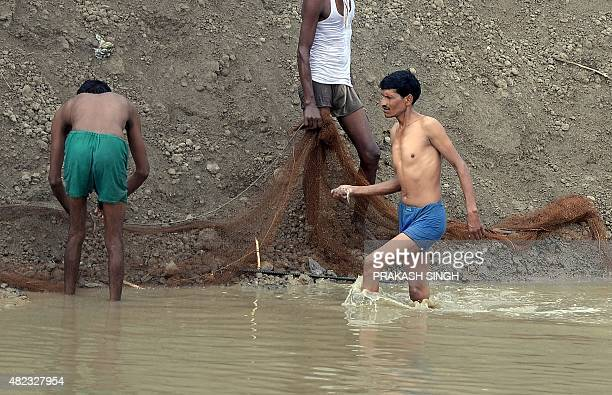 Indian men catch fish in a dried up canal on the outskirts of New Delhi on July 30 2015 AFP PHOTO/PRAKASH SINGH