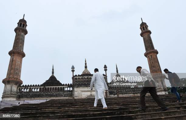 Indian men climb the stairs next to the mosque at the Bara Imambara a colossal imambara complex in Lucknow northern India on August 25 2017 / AFP...