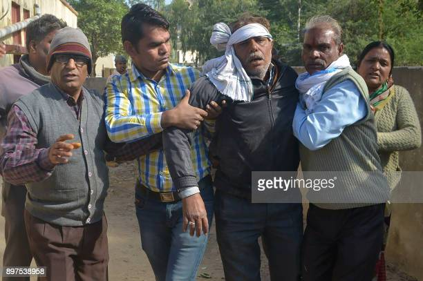 Indian men escort an injured bus passenger after an accident in Sawai Madhopur some 160 kilometres from Jaipur in Rajasthan state on December 23 2017...