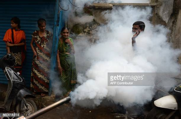 TOPSHOT Indian men gestures as a municipal worker fumigates an area to prevent mosquitos from breeding in Chennai on October 12 2017 Several cases of...