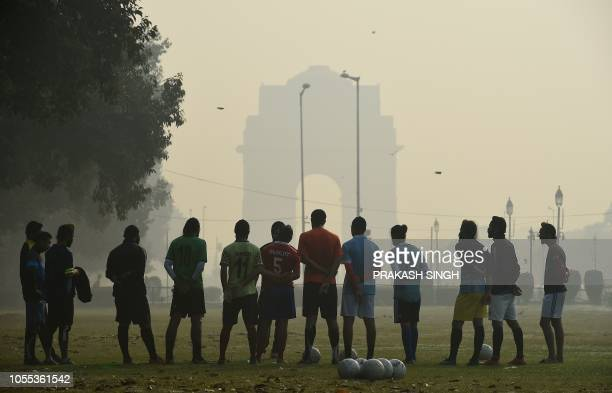 Indian men gets tips from a football coach on the India Gate lawn amid heavy smog conditions in New Delhi on October 30 2018 Smog levels spike during...