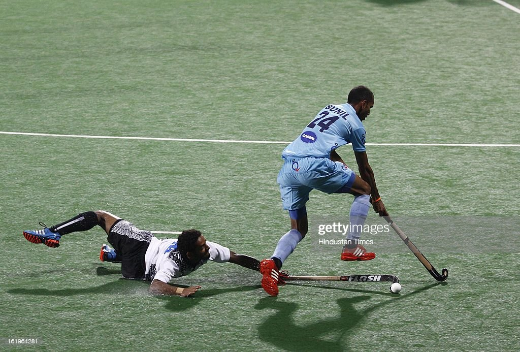 Indian Men Hockey Player Sunil manuver the ball as Fiji player Tackles during the Hockey World League Round 2 at Dhyan Chand Stadium on February 18, 2013 in New Delhi, India. It was a complete domination by Indian side as they trounced the Fijian side 8-0.