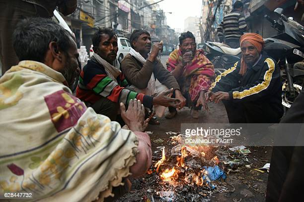 Indian men huddle around a fire to keep warm at the roadside on a cold foggy morning in New Delhi on December 8 2016 / AFP / Dominique FAGET