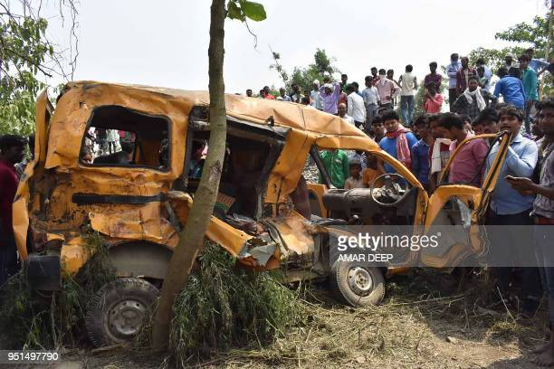Indian men inspect a school van that was hit by a train at an ungated railroad crossing near Kushinagar district of Uttar Pradesh on April 26 2018 At...