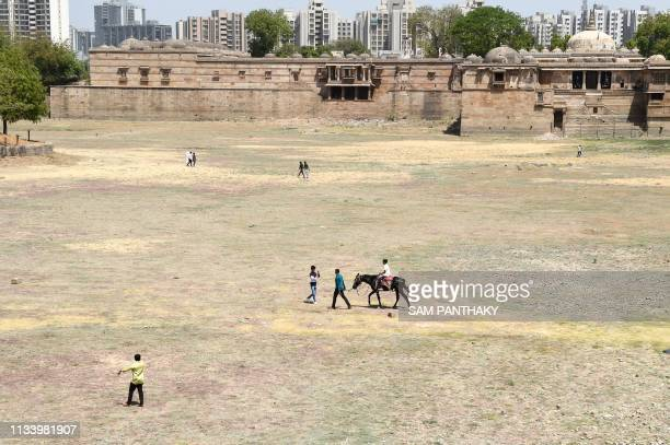 Indian men leading a horse walk on the dry land of the Ahmad Sar Lake at Sarkhej Roza the 15th century complex which is constituted of a mosque and...