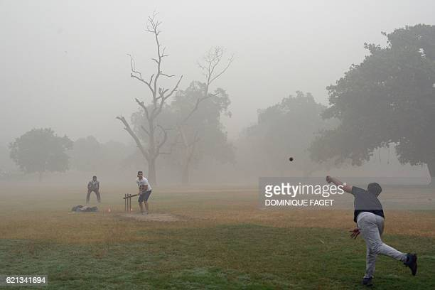Indian men play cricket amid heavy smog in New Delhi on November 6 2016 Thick smog has blanketed the capital for days with local and central...