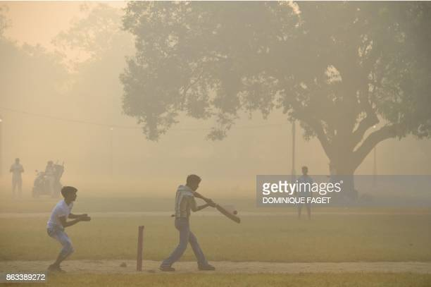 Indian men play cricket amid heavy smog in New Delhi on October 20 2017 the day after the Diwali Festival New Delhi was shrouded in a thick blanket...