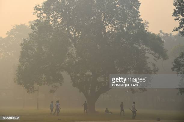 TOPSHOT Indian men play cricket amid heavy smog in New Delhi on October 20 2017 the day after the Diwali Festival New Delhi was shrouded in a thick...