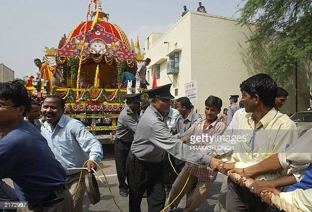 Indian men pull a chariot during the Jagannath Rath Yatra festival in New Delhi 01 July 2003 During the festival images of Jagannath his brother...