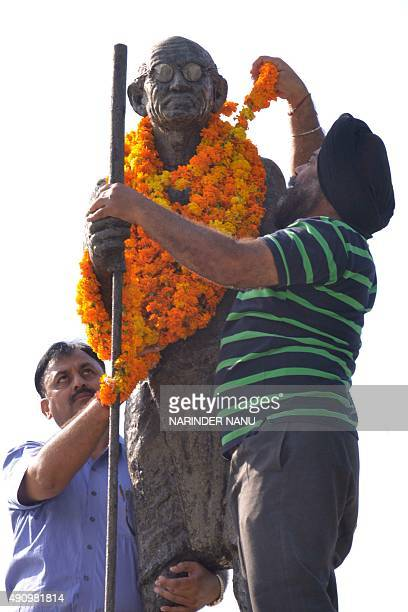 Indian men put garlands on a statue of Mahatma Gandhi in Amritsar on October 2 on the occasion of Gandhi's 146th birth anniversary Indians all over...