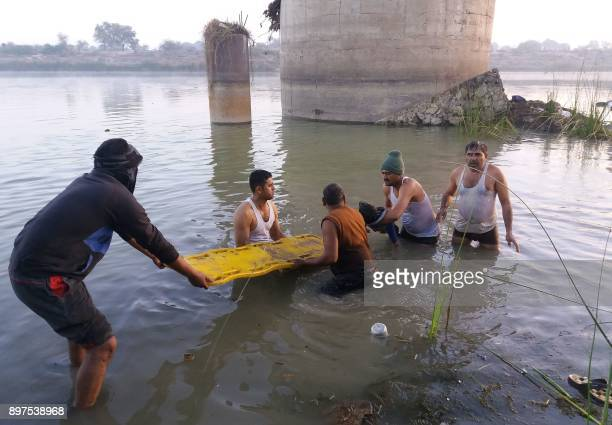 TOPSHOT Indian men recover the body of a child from the Banas River at the site of a bus accident in Sawai Madhopur some 160 kilometres from Jaipur...