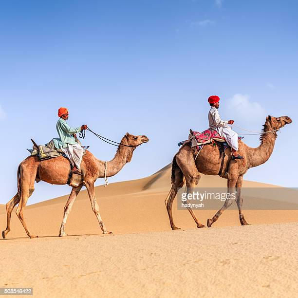 Indian men riding camels on sand dunes, Rajasthan, India