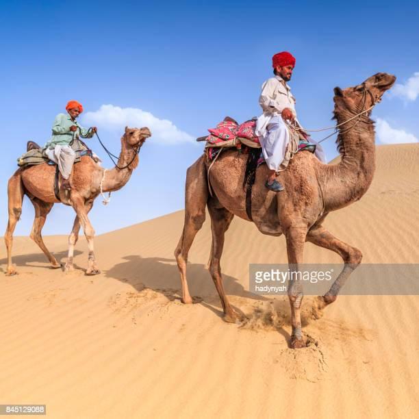 Indian hombres camellos en sand dunes, Rajastán de India