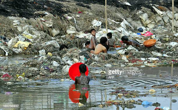 Indian men search for coins and gold in the polluted waters of the Ganga river at Sangam after the Kumbh Mela festival in Allahabad on April 2 2013...