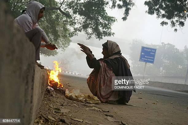 Indian men sit around a fire to keep warm at the roadside on a cold foggy morning in New Delhi on December 8 2016 / AFP / Dominique FAGET