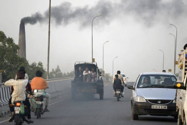 Indian men sit in the back of a truck on a highway in Jalandhar on June 4 on the eve of World Environment Day The UN declared the 2017 theme for...