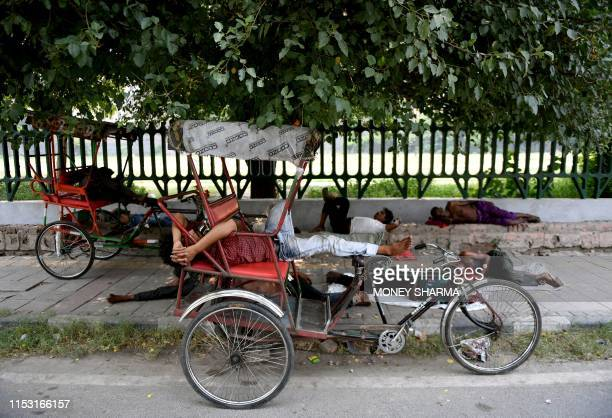 Indian men take an afternoon nap under a tree during a hot summer day in New Delhi on July 2, 2019.