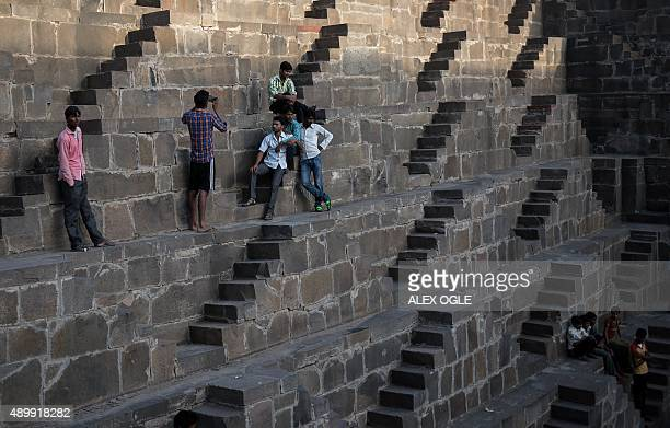 Indian men take photos of each other at the historic Chand Baori stepwell in Abhaneri village in Rajasthan on September 24 2015 For a few hours on...