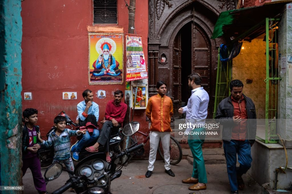 Indian men talk in the corner of an alley in the old quarters of New Delhi on February 21, 2018. /