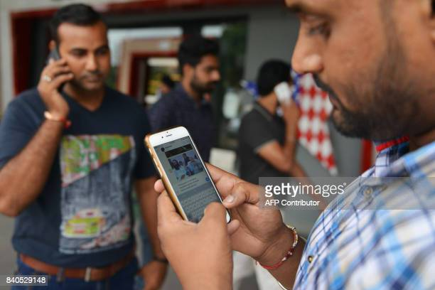 Indian men use their mobile phones after local autorithies shut down internet services in the state of Punjab during the unrest by followers of...