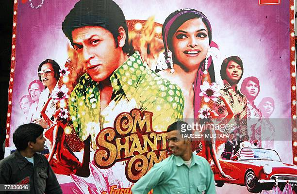 Indian men walk by a poster for the Bollywood film 'Om Shanti Om' outside a cinema hall in New Delhi 10 November 2007 Film enthusiasts turned up in...
