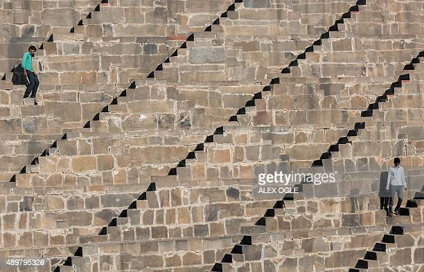 Indian men walk down the steps of the historic Chand Baori stepwell in Abhaneri village of western Rajasthan state on September 24, 2015. For a few...