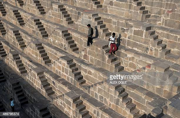 Indian men walk down the steps of the historic Chand Baori stepwell in Abhaneri village of western Rajasthan state on September 24 2015 For a few...