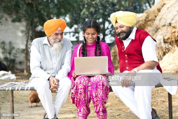 indian men with girl using laptop - punjab india stock pictures, royalty-free photos & images
