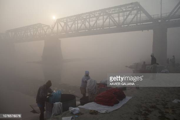 Indian men work in an open air laundry on the banks of the Yamuna River amid heavy fog and smog conditions at Haathi Ghat in Agra in the Indian state...