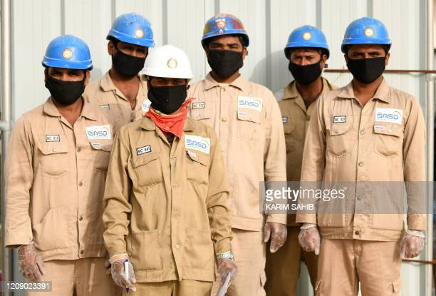 Indian men working for a public services company in the United Arab Emirates pose for a picture with their protective gear masks and gloves during...