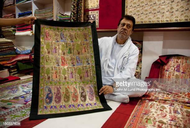 Indian merchant shows his ornate carpets, Rajasthan, India