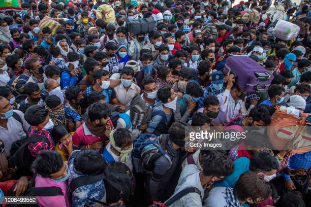 Indian migrant workers and labourers along with their families stuck in the national capital, with and without protective masks crowd to board buses...