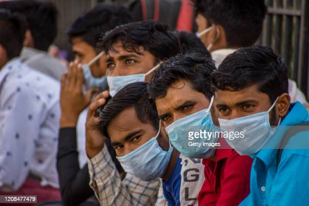 Indian migrant workers covering their faces with protective masks wait to board buses to return to their native villages as a nationwide lockdown...