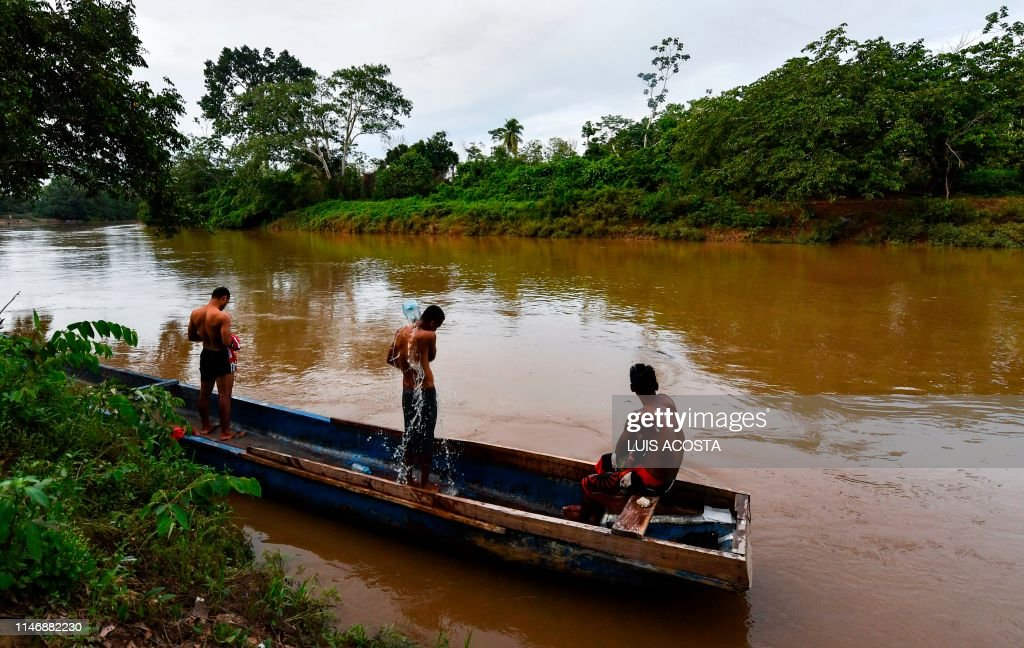 Indian migrants bathe in the Chucunaque River at the