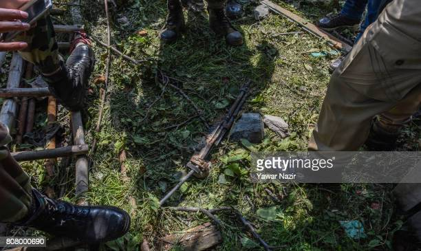 Indian military forces inspects a charred rifle of a killed rebel after a gun battle between Indian government forces and rebles on July 4 2017 in...