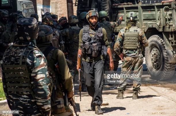 Indian military forces loom towards the residential house where Kashmiri Muslim rebels have taken refuge during a gun battle between Indian armed...
