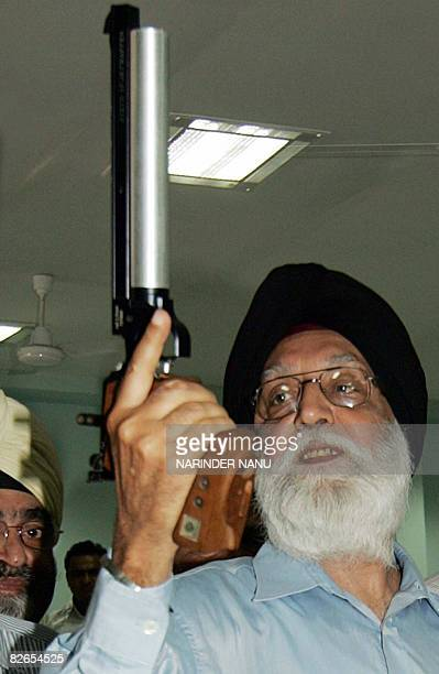Indian Minister for Sports and Youth Affairs Manohar Singh Gill holds a pistol while posing for media representatives during the inauguration of an...