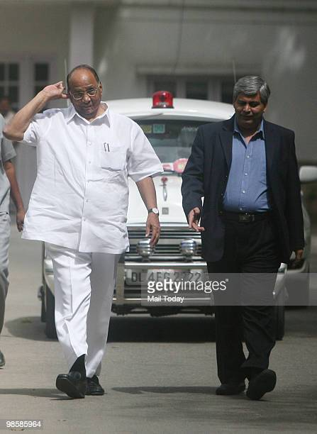 Indian Minister of Agriculture Sharad Pawar and Board of Control for Cricket in India chief Shashank Manohar walk following a meeting at Pawar's...