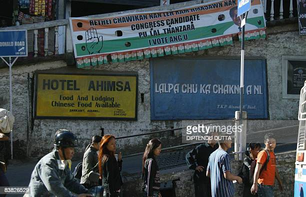 Indian Mizo people wait at a bus stop near an election campaign banner in Aizawl the capital city of the northeastern Indian state of Mizoram on...
