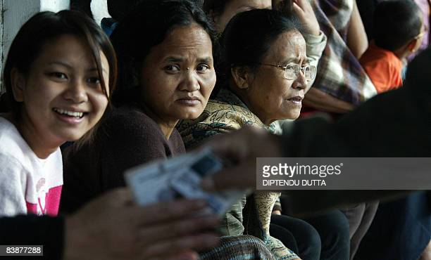 Indian Mizo women watch as voters hand over voting identity cards as they wait at a polling station in Aizawl capital of the northeastern state of...