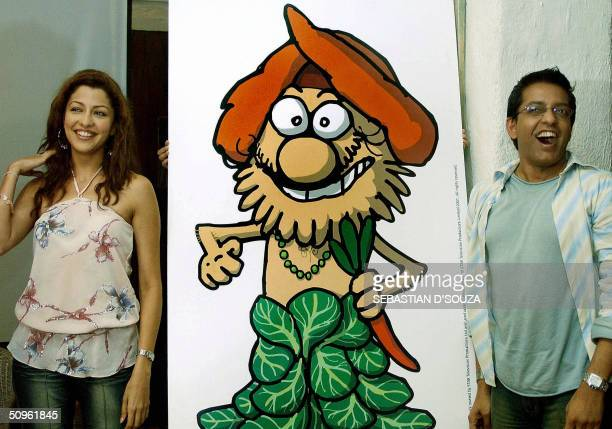 Indian model and former Miss India Aditi Govitrikar and fashion designer Hemant Trevedi poses next to PETA's new print advertisement showing Prof...