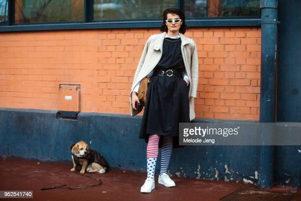 Indian model Dipti Sharma poses with a dog and wears white futuristic sunglasses white coat a black dress with a belt stripe and polka dot stockings...