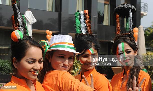 Indian models dressed in the nation's tricolor and with their hair styled in the Cricket World Cup trophy cricket ball cricket bat wickets and...