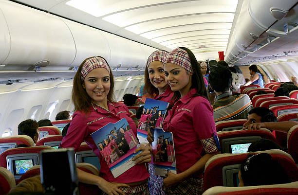 Indian models pose in uniforms of the `FlyingCats` Air Hostess training school on an aircraft enroute to Chandigarh10 August 2006 With centres across.