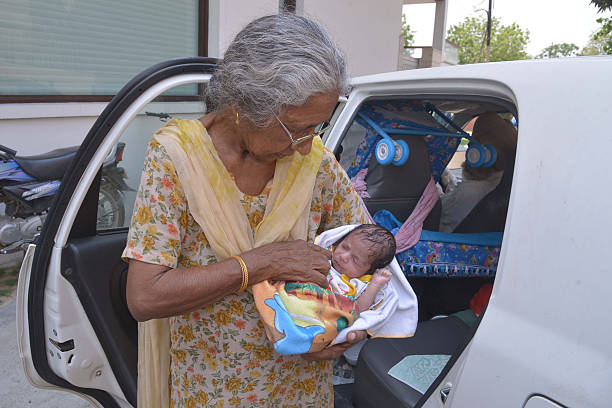 Indian mother Daljinder Kaur poses for a photograph as she holds her newborn baby boy Arman as she arrives home in Amritsar on May 11 2016 An Indian..