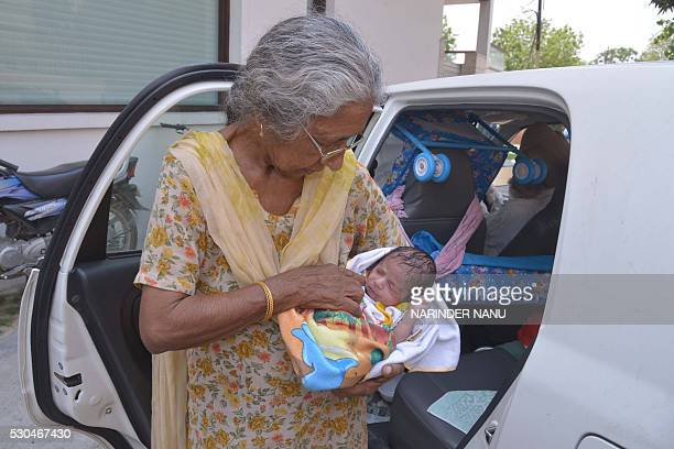 Indian mother Daljinder Kaur poses for a photograph as she holds her newborn baby boy Arman as she arrives home in Amritsar on May 11 2016 An Indian...