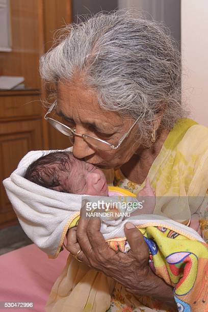 Indian mother Daljinder Kaur poses for a photograph as she holds her newborn baby boy Arman at their home in Amritsar on May 11 2016 An Indian woman...