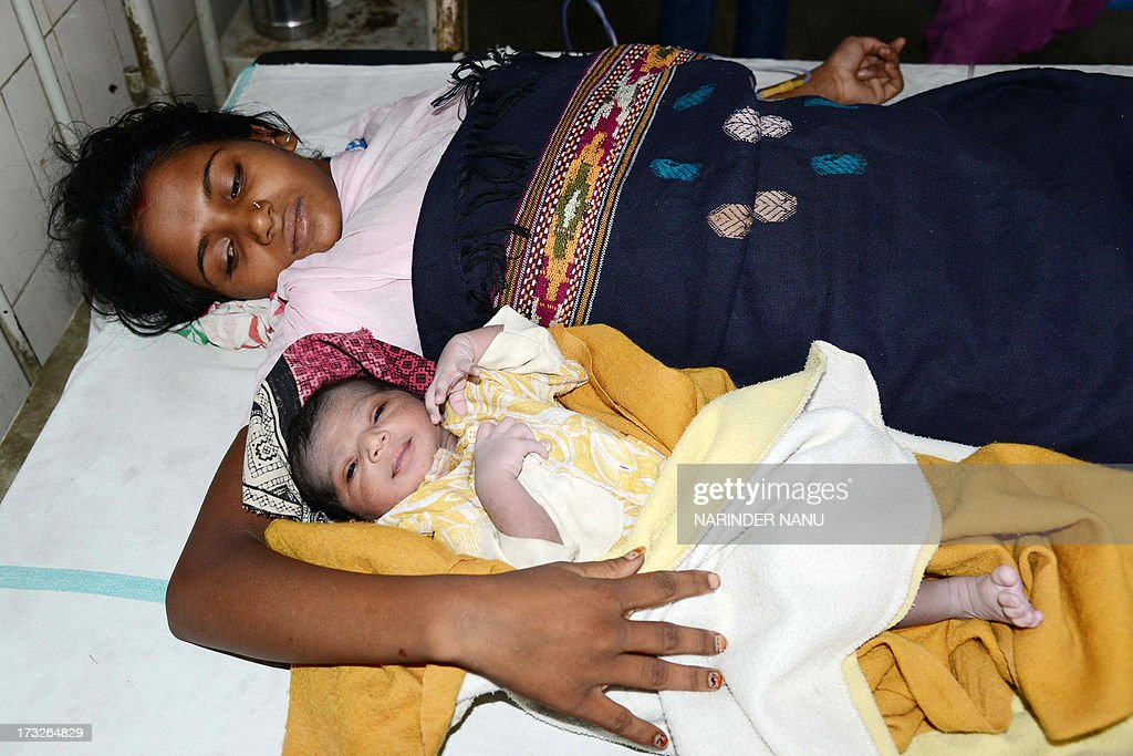 Indian mother Geeta looks on as her newborn baby girl rests at a government hospital in Amritsar on July 11 on the occasion of World Population Day...