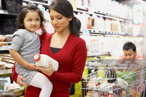 Indian mother grocery shopping with children